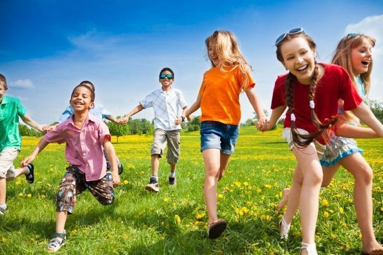 seven kids running in grass