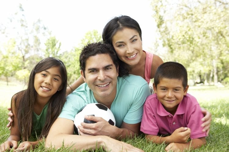 family smiling with soccer ball