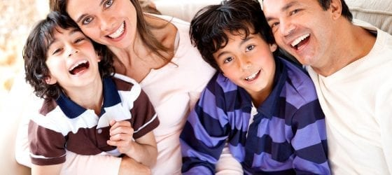 family smiling sitting on couch