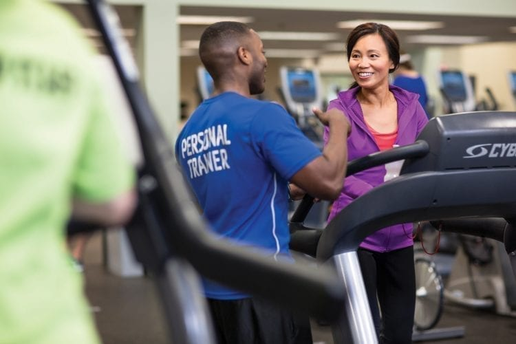 woman working out on treadmill with personal trainer