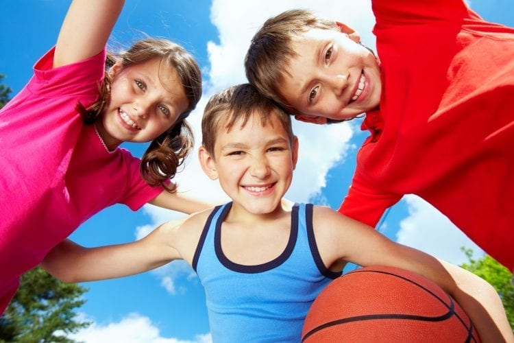 three kids smiling with basketball looking down at camera