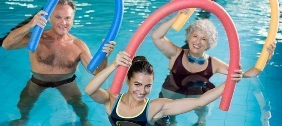 three adults doing water fitness class